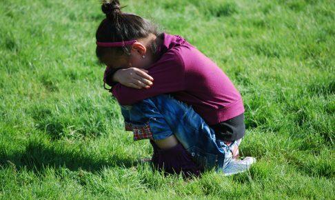 草原でしゃがんで泣いている女の子
