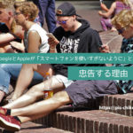 スマートフォンを触りながら外に座っている若者達
